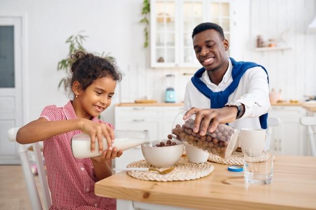 Szczęśliwy ojciec i córka mają śniadanie w domu. uśmiechnięta rodzina je rano w kuchni. tata karmi dziecko płci żeńskiej, dobry związek