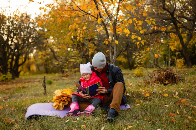 Szczęśliwy ojciec i córka siedzi książkę w jesień parku na żółtych liściach i czyta