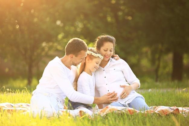 Szczęśliwy ojciec i córka w ciąży mama na pikniku,