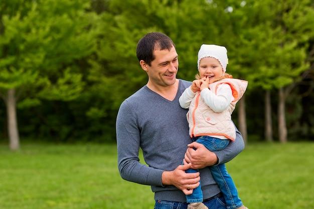 Szczęśliwy ojciec i córka w parku z uśmiechem uśmiechem i szczęściem
