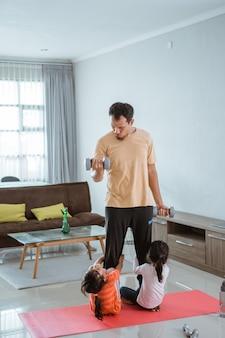 Szczęśliwy ojciec i dziecko razem robią ćwiczenia. portret zdrowego treningu rodzinnego w domu. dziecko przeszkadza tacie podczas uprawiania sportu