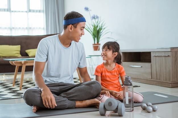 Szczęśliwy ojciec i dziecko razem robią ćwiczenia. portret zdrowego treningu rodzinnego w domu. mężczyzna i jego córka sport