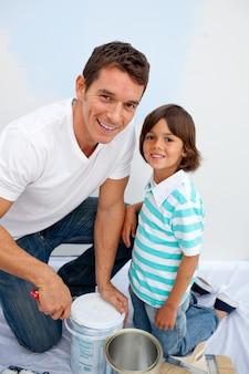 Szczęśliwy ojciec i jego syn malujący w ich nowym domu