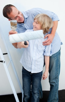 Szczęśliwy ojciec i jego syn maluje ścianę