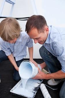 Szczęśliwy ojciec i jego syn przygotowywa farbę