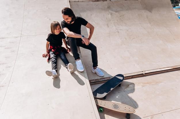 Szczęśliwy ojciec i jego syn ubrani w zwykłe ciuchy siedzą i śmieją się na zjeżdżalni w skateparku obok deskorolek w słoneczny dzień.