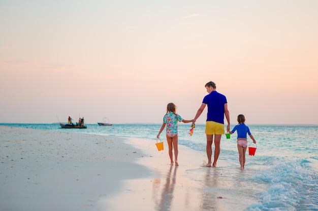 Szczęśliwy ojciec i jego urocze córeczki na tropikalnej plaży zabawy