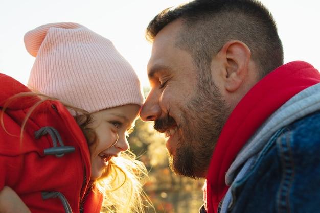 Szczęśliwy ojciec i mała śliczna córka biegnąca leśną ścieżką w jesienny, słoneczny dzień. czas z rodziną, togehterness, rodzicielstwo i koncepcja szczęśliwego dzieciństwa. weekend połączony ze szczerymi emocjami.