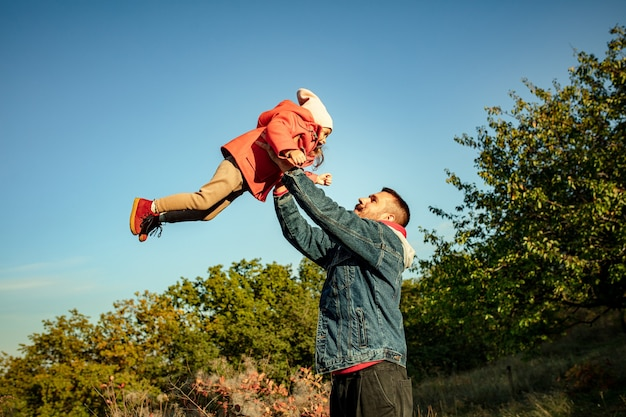 Szczęśliwy ojciec i mała słodka córka idąc leśną ścieżką w jesienny słoneczny dzień