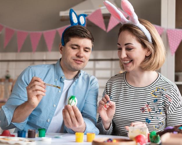 Szczęśliwy ojciec i matka maluje easter jajka