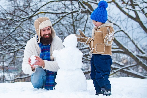 Szczęśliwy ojciec i syn bałwana w śniegu
