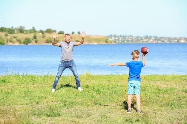 Szczęśliwy ojciec i syn gra w rugby w pobliżu rzeki