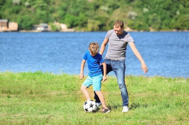 Szczęśliwy ojciec i syn grający w piłkę nożną w pobliżu rzeki