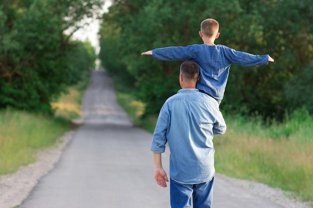 Szczęśliwy ojciec i syn idą wzdłuż drogi lecą