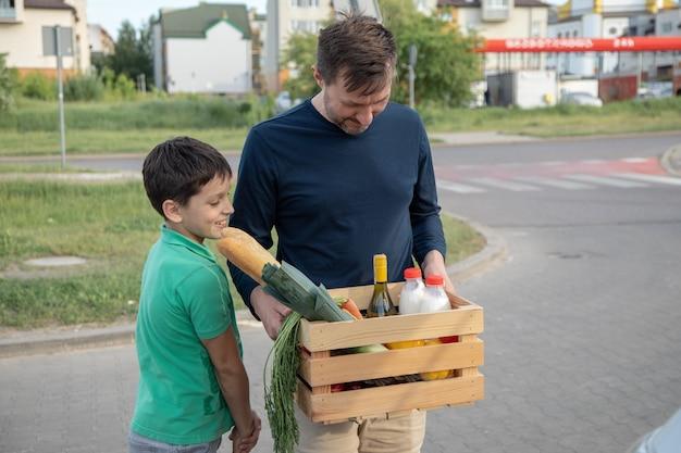 Szczęśliwy ojciec i syn niosą jedzenie w drewnianym pudełku. pojęcie wygody i przyjazności dla środowiska