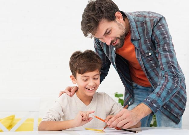 Szczęśliwy ojciec i syn odrabiania lekcji