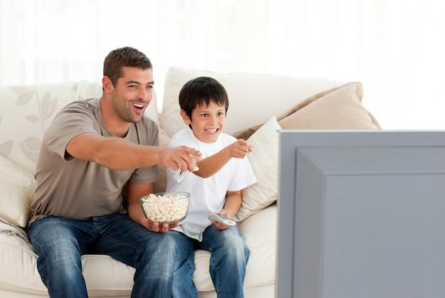Szczęśliwy ojciec i syn oglądanie telewizji podczas jedzenia kukurydzy pop