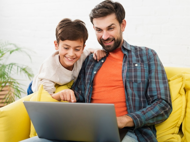 Szczęśliwy ojciec i syn patrzeje na laptopie