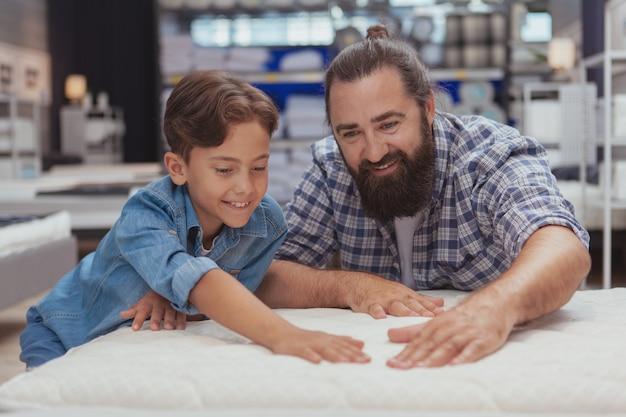 Szczęśliwy ojciec i syn robi zakupy przy wydziałowym sklepem