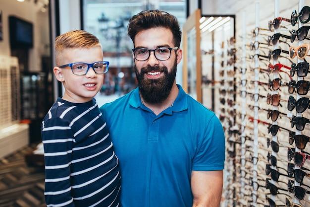 Szczęśliwy ojciec i syn wybierając oprawki do okularów w sklepie optycznym.