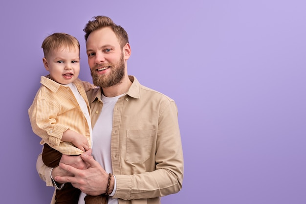 Szczęśliwy ojciec i synek pozowanie na kamery uśmiechnięty, młody tata rodziny kaukaski i syn w casual na białym tle na fioletowym tle
