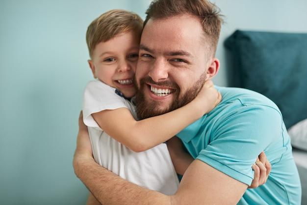 Szczęśliwy ojciec i synek przytulanie w sypialni
