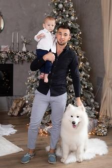 Szczęśliwy ojciec i urocza mała chłopiec w domu. boże narodzenie, nowy rok, zima i święta koncepcja sezonów. rodzina.