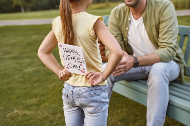 Szczęśliwy ojciec ojca siedzi na drewnianej ławce w parku, podczas gdy jego mała córka się ukrywa