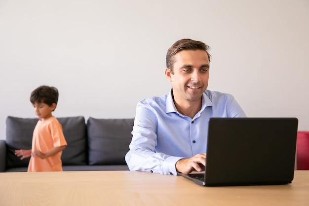 Szczęśliwy ojciec przeglądający internet, gdy chłopiec bawi się blisko niego. kaukaski tata przy użyciu komputera przenośnego i pracy w domu.