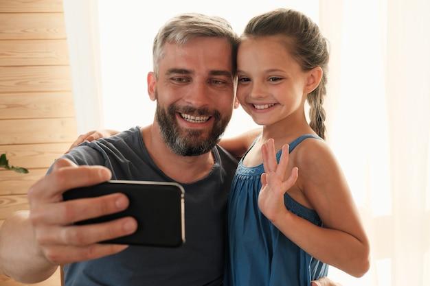 Szczęśliwy ojciec robi selfie portret w swoim telefonie komórkowym z jego małą dziewczynką oni uśmiechają się