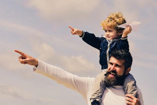 Szczęśliwy ojciec rodziny i dziecko na łące z latawcem w lecie na naturze
