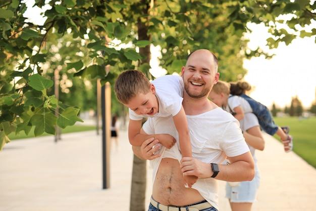 Szczęśliwy ojciec rodziny i syn, zabawy w parku. mężczyzna trzymający dziecko na ramionach