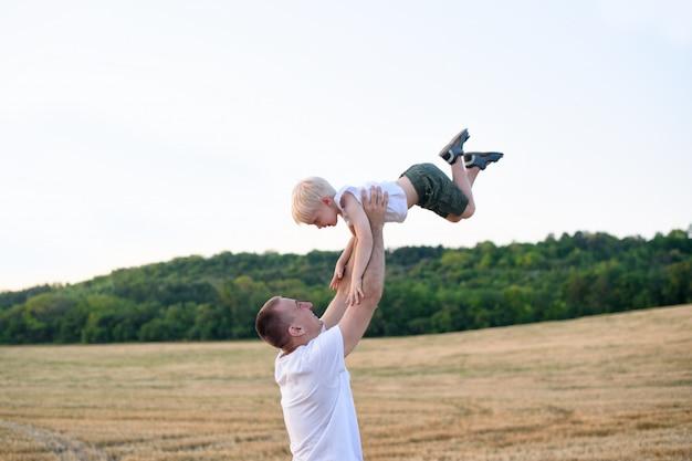 Szczęśliwy ojciec rzuca małego blond chłopca na skoszone pole pszenicy. czas zachodu słońca