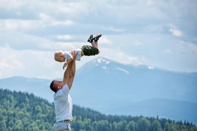 Szczęśliwy ojciec rzuca małego syna na zielony las, góry i niebo z chmurami