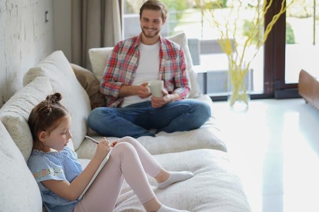 Szczęśliwy ojciec smilling córka siedzi na kanapie ciesząc się aktywnością twórczą, rysując piórkiem zdjęcia w albumach, ojciec i córka spędzają razem wolny czas.