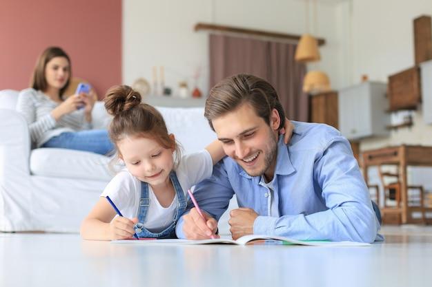 Szczęśliwy Ojciec Smilling Córkę Leżącą Na Ciepłej Podłodze Ciesząc Się Twórczą Aktywnością, Rysowanie Ołówkiem, Kolorowanie Zdjęć W Albumach, Matka Odpoczywa Na Kanapie, Rodzina Spędza Razem Wolny Czas. Premium Zdjęcia