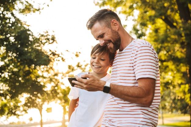 Szczęśliwy ojciec spędzający czas ze swoim małym synkiem w parku