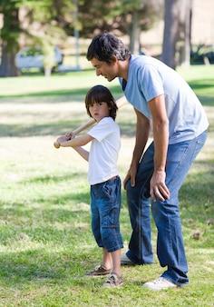 Szczęśliwy ojciec uczy baseball jego syna