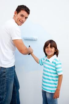 Szczęśliwy ojciec uczy syna, jak malować