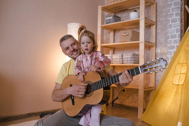 Szczęśliwy ojciec z córeczką uczy się gry na gitarze siedząc w domu na podłodze obok żółtego tipi. szczęśliwy ojciec