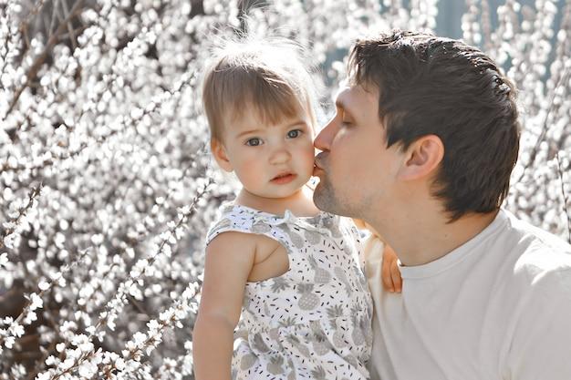 Szczęśliwy ojciec z córką spaceruje po kwietnej łące. miłość i wiosenne kwitnienie. mężczyzna i mała dziewczynka. dzień ojca