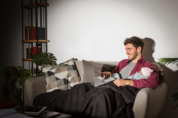 Szczęśliwy ojciec z dzieckiem używa laptop w wieczór