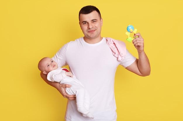 Szczęśliwy ojciec z małą córeczką w domu, grając razem, młody tata z grzechotką opiekuje się córką, pozując na białym tle nad żółtą ścianą.