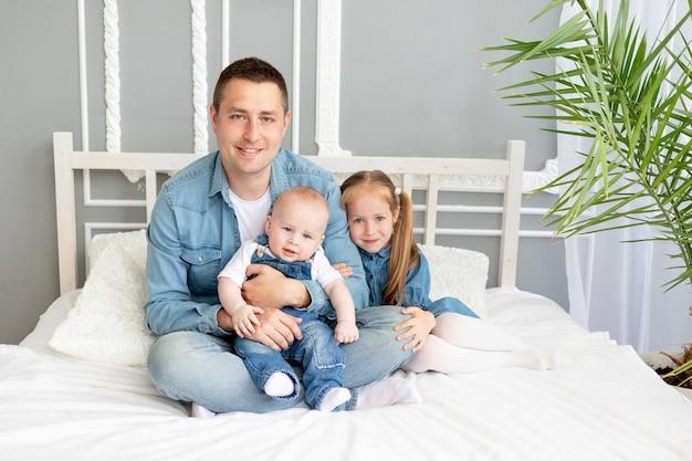 Szczęśliwy ojciec z synem i córką dzieci przytulają się na łóżku w koncepcji domu