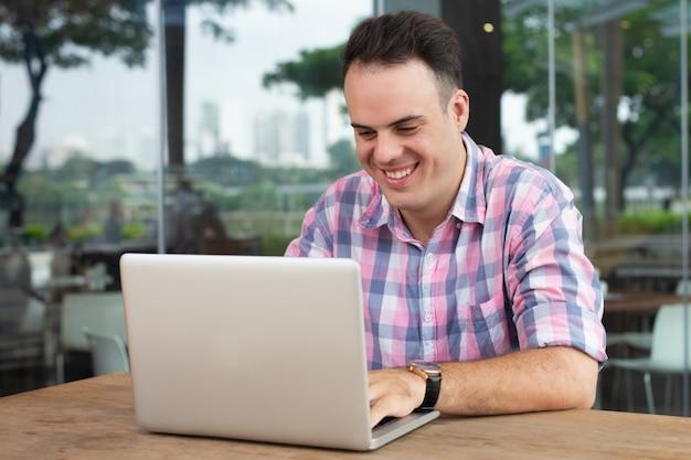 Szczęśliwy optymistyczny freelancer pracuje z laptopem w plenerowej kawiarni