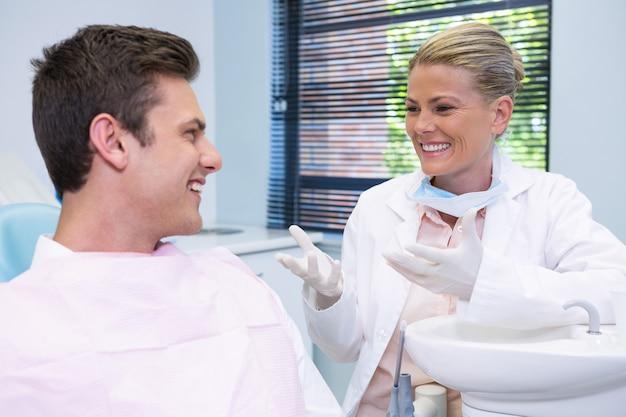 Szczęśliwy pacjent rozmawiający z dentystą