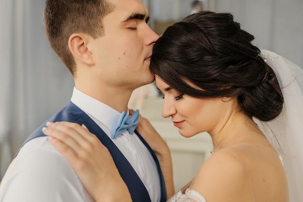 Szczęśliwy pan młody całuje pannę młodą w czoło. piękna elegancka para w rocznika wnętrzu. koncepcja ślubu. szczęśliwa para nowożeńców.