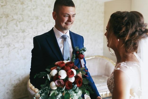 Szczęśliwy pan młody wyciąga rękę z czerwonym bukietem ślubnych do wspaniałej narzeczonej