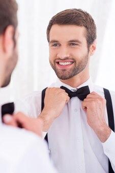 Szczęśliwy pan młody. zbliżenie: młody mężczyzna w białej koszuli poprawia muszkę i uśmiecha się stojąc przed lustrem