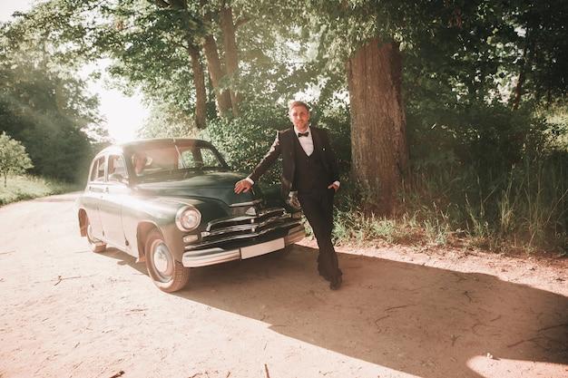 Szczęśliwy pana młodego stojącego w pobliżu samochodu podczas podróży weselnej. ślub w stylu retro